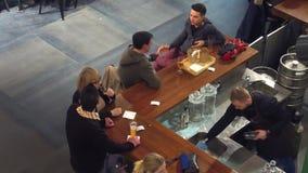 WARSZAWA POLSKA, GRUDZIEŃ, -, 22, 2016 Młodzi ludzie ma napoje Wiszący przy barem out, widok od above Obrazy Stock