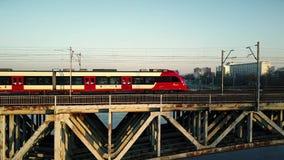 WARSZAWA POLSKA, MARZEC, -, 27, 2017 Antena strzelał czerwony pociąg pasażerski poruszający na kolejowym moscie przez rzekę Obrazy Stock