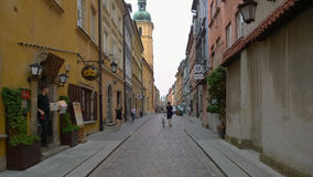 Warszawa. Street in Warszawa Old Town. Woman walking with dog through one of the streets in Warszawa Old Town Stock Photography
