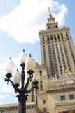 Warszawaslott av kultur och vetenskap med svartvita gataljus framme på en solig dag royaltyfri bild