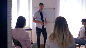 Warsztat na psychologii, mężczyzna psycholog prowadzi szkolenie dla młodzi ludzie na tło desce z słowem - problemy zbiory wideo