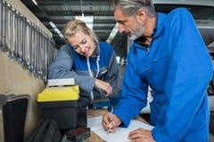 Warsztatowi mechanicy patrzeje papiery fotografia royalty free