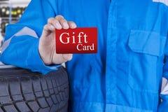 Warsztatowy pracownik trzyma prezent kartę Zdjęcie Stock