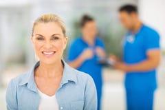 Warteüberprüfung der mittleren Greisin in der Arztpraxis Lizenzfreie Stockbilder