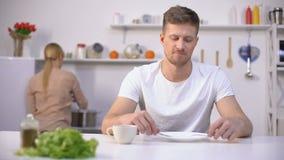 Warteabendessen des positiven Mannes, junge Frau, die Suppe auf Hintergrund, Hunger kocht stock video