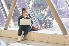 Wartearbeiten des jungen männlichen Unternehmerstudenten an Laptop im sunn lizenzfreies stockfoto