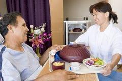 Warten Sie das Dienen einem Patienten einer Mahlzeit in seinem Bett lizenzfreie stockfotografie