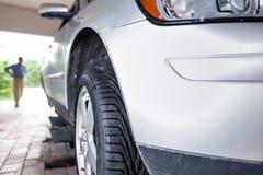 Wartender Kunde, während sein Auto in einer Garage geprüft wird Stockfotografie
