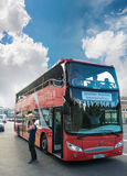 Wartetouristen des roten Doppeldeckerstadtbesichtigungs-Busses auf D stockbild