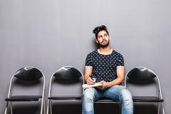 WarteVorstellungsgespräch des jungen indischen Mannes in der Aufnahmehalle lizenzfreies stockfoto