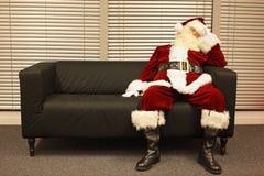 Warteweihnachtsjob, Weihnachtsmann, der auf Sofa schläft Lizenzfreie Stockfotos