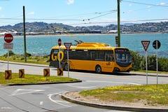 Wartezeiten eines gelbe elektrische Busses an der Endstation durch die Seite von Lyall-Bucht, Wellington, Neuseeland lizenzfreie stockfotos