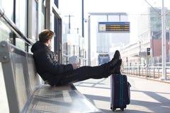 Wartezug des jungen Mannes an der Station stockfotos