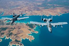 A-10 Warthogs soar over the resevoir. A pair of Republic A-10`s soar over a reservoir while holding close formation Royalty Free Stock Photos