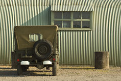 Wartime scene. A wartime jeep is parked outside a period military building stock photo