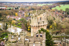 Warwick Castle and town. Parts of the wall of Warwick castle with some medieval towers and parts of Warwick town in the background Royalty Free Stock Photos
