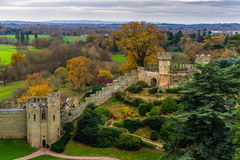 Warwick Castle wall. Parts of the wall of Warwick castle with some medieval towers and colorful trees in the background Royalty Free Stock Images