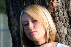 Wary Blond. Head and shoulders shot of a serious young blond woman with a wary expression, standing in front of a large tree Royalty Free Stock Photo