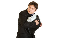 Wary businessman hugging briefcase with money Stock Photo