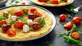 Warzyw jajek Omelette z pomidorami, dzika rakieta, grecki ser, oliwki w talerzu Ranku śniadaniowy zdrowy jedzenie Fotografia Stock