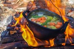 Warzywa przygotowywali w kotle nad ogieniem na naturze Obrazy Royalty Free