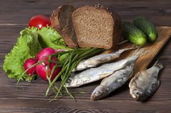 Warzywa, zielenie, chleb i ryba na drewnianym wieśniaka stole, Zdjęcia Stock