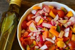 Warzywo sałatka i butelka oliwa z oliwek na drewnianym tle obrazy stock