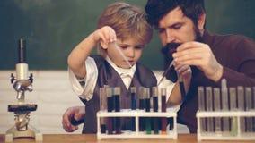 Was in der Chemie unterrichtet wird Lehrer unterrichtet einen Studenten, ein Mikroskop zu benutzen Wissenschafts- und Bildungskon stock video footage