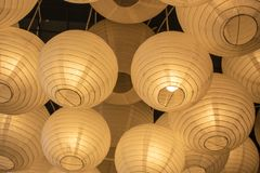 It was filmed inside the restaurant. Paper lamps in yellow color. There's more than one. Light, asian, background, chinese, culture, decoration, design royalty free stock image