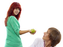 Was frightened. Young attractive girl gives a green apple to her boy Royalty Free Stock Image