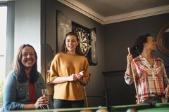That Was a Great Game. Small group of female friends playing a game of pool in a games room in a house royalty free stock images