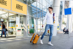 That was really great vacation. Happy young man arrived from trip. He is walking from airport with luggage and smiling. Guy is looking back and smiling Royalty Free Stock Images