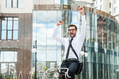 It was successful day!. Low angle view of cheerful young businessman keeping arms raised and expressing positivity while riding on his bicycle royalty free stock photo