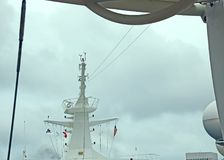 THIS WAS THE TOP OF THE CRUISE SHIP LIBERTY. THIS IS ARTISTICALLY DESIGNED TOP OF THE CRUISE SHIP LIBERTY. FLAGS DISPLAYED LOVELY DESIGN. BLUE SKY CLOUDS IT Stock Photos