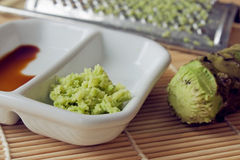 Wasabi. Selective focus image of grated fresh wasabi root also called Japanese horseradish on a bamboo mat with soy sauce Royalty Free Stock Photo
