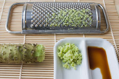 Wasabi. Selective focus image of grated fresh wasabi root also called Japanese horseradish on a bamboo mat with soy sauce and a grater Royalty Free Stock Images