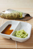 Wasabi. Selective focus image of grated fresh wasabi root also called Japanese horseradish on a bamboo mat with soy sauce Royalty Free Stock Photos