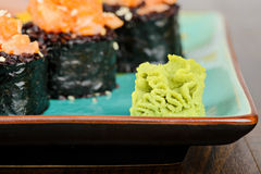 Wasabi with baked sushi rolls on turquoise plate Stock Photos