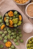 Wasabi coated peanuts. Wasabi coated peanuts with spice on wooden table royalty free stock image
