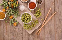 Wasabi coated peanuts. Wasabi coated peanuts with spice on wooden table stock photo