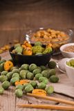 Wasabi coated peanuts. Wasabi coated peanuts with spice on wooden table stock image