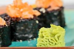 Wasabi com rolos de sushi cozidos na placa de turquesa Fotos de Stock Royalty Free