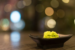 Wasabi in der schwarzen Untertasse auf Holztisch mit Schärfentiefe Effekt, japanische Lebensmittel ` s Würze, bokeh Hintergrund Lizenzfreies Stockfoto