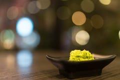 Wasabi em uns pires pretos na tabela de madeira com profundidade do efeito de campo, condimento japonês do ` s do alimento, fundo foto de stock royalty free