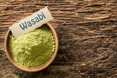 Wasabi. A pungent green Japanese condiment made from the root of the herb Eutrema , dried and powdered in a bowl standing on a textured weathered surface with Stock Photo