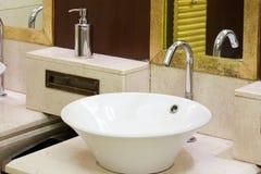 Wasbakken, kranen en spiegel in openbaar toilet Stock Afbeelding