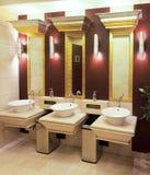 Wasbakken, kranen en spiegel in openbaar toilet Stock Fotografie
