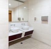 Wasbakken, kranen en spiegel in openbaar toilet Stock Foto