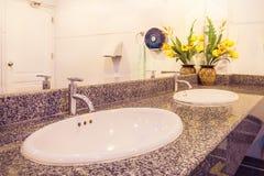 Wasbassin met oranje licht in badkamers Stock Foto's