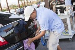 Waschanlageangestellter, der Rückseite eines Fahrzeugs abwischt Stockbild
